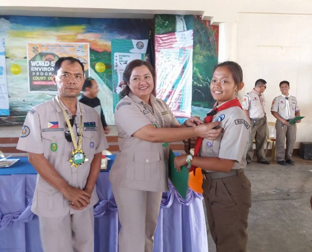 SDS Carmela Tamayo of DepEd Biliran (center) with OIC John Anthony Romagos of BSP Biliran Council (left) awards the WSEP Badge to a female Senior Scout. (Photo by Alma M. Atibula)